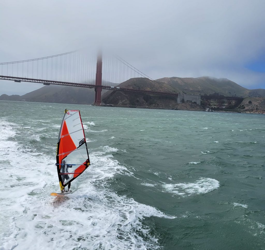 sailor in the Bay conquering waves, Goden Gate bridge in the horizon